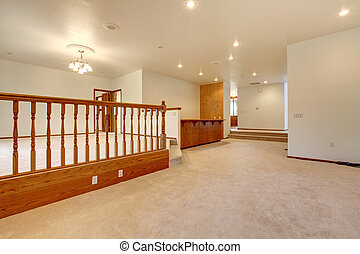 Large empty room with beige carpet and railing. - Large...