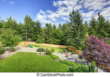 Large fenced backyard with patio and play set.