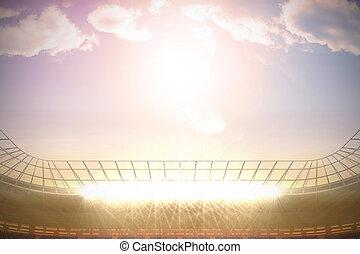 Large football stadium with spotlights under morning sky