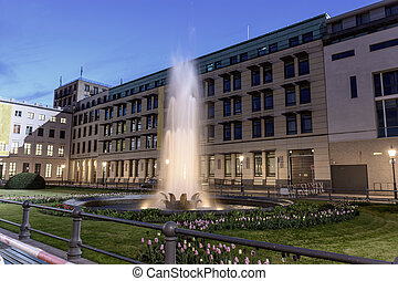 Large fountain in front of a beautiful building, on the lawn blossom tulips