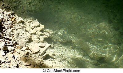 Large fragments of rock in water of mountain lake water....