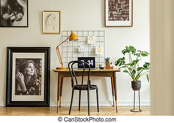 Large, framed photo and a monstera plant in a classic workspace interior with an orange lamp on a wooden desk