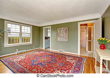 Large front room with chic decor and green walls.