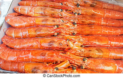 Large frozen langoustines in a package on the counter of a fish market, close-up.