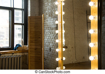 Large full-length mirror in a room with a brick wall and a window