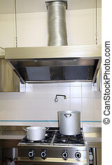fume Extractor hood in the industrial kitchen with pots on the stove top