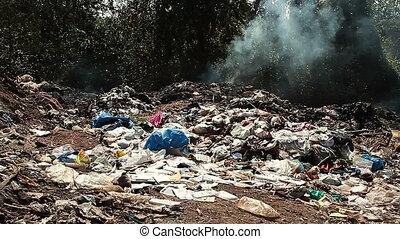 Large garbage dump waste with smoke