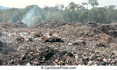 Large garbage dump waste with smoke