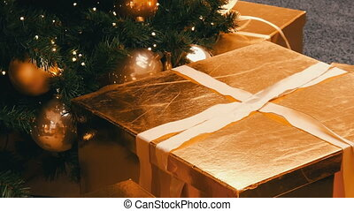 Large gift boxes, present of gold color under the Christmas...