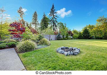 Large green backyard with beautiful landscape.