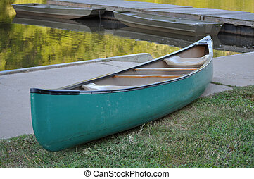 A large green canoe sits empty next to the water.