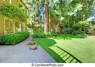 Large green summer back yard and brown house.