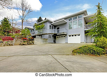 Large grey modern home exterior with large driveway.