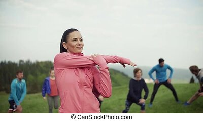Large group of fit and active people doing exercise in...