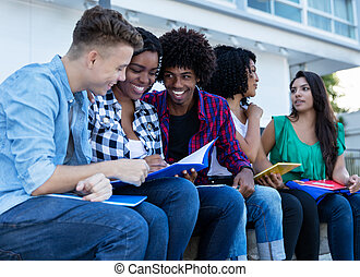 Large group of international students learning outdoors on...