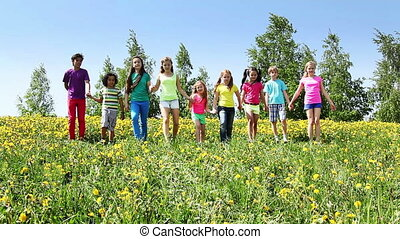Large group of kids run in dandelion field holding hands at sunny spring day