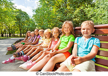 Large group of kids sitting on the bench