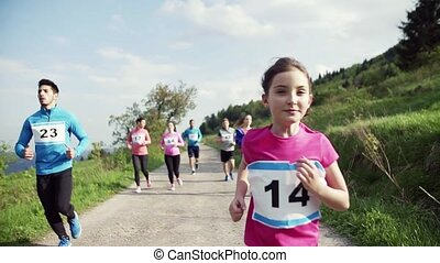 Large group of multi generation people running a race...