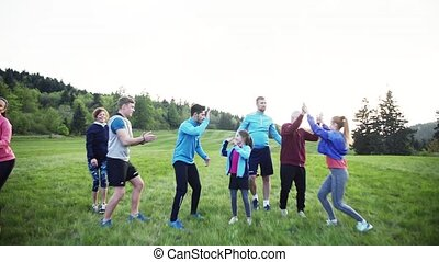 Large group of people cross country jumping in nature at...