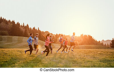 Large group of people cross country running in nature.