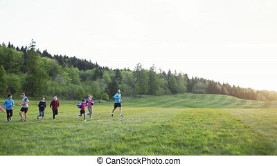 Large group of people cross country running in nature. - A...