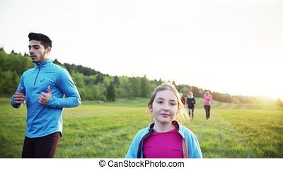Large group of people cross country running in nature at...