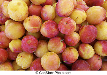 large group of red plums for sale in a market on the island of madeira