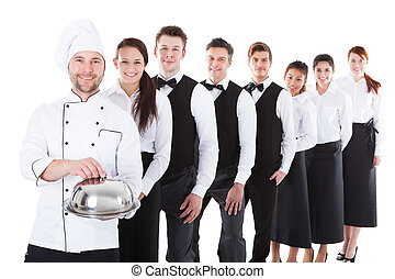 Large group of waiters and waitresses standing in row