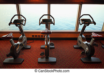 large gym hall with exercise bicycle near window with view on sea in cruise ship