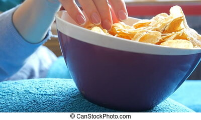 Large hand of an elderly man eats potato chips from a huge...