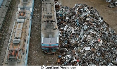 large heaps of metal scrap and containers with garbage are...