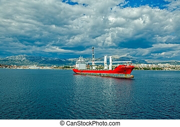 A large heavy lift ship anchored in front of the port.