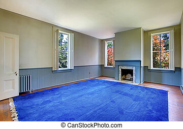 Large historical living room with blue rug and fireplace