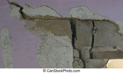 Large holes and cracks in a concrete wall