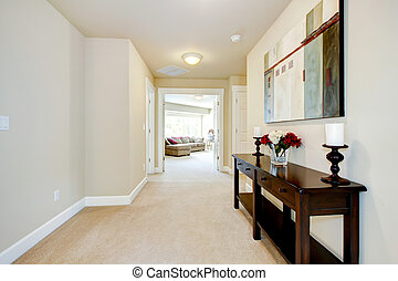 Large home hallway with art and furniture, beige carpet.