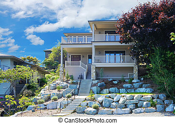 Large house with balconies on the hill with rocks.