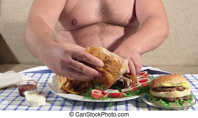 Large hungry person eating fat fried chicken with french fries at home