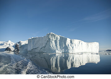 Large iceberg and its reflection in the southern ocean on a summer day.