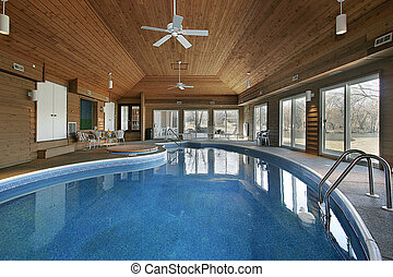 Large indoor swimming pool with wood ceiling
