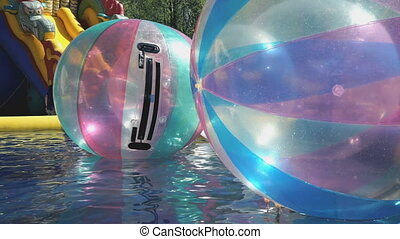 Large inflatable balls floating in swimming pool