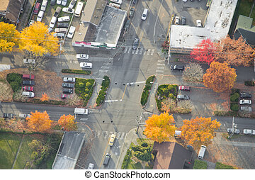 Aerial view of traffic passing through bright intersection at sunset