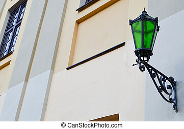 Large iron metallic green high street lamp, lighting against the background of a stone old building
