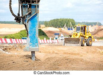 Large jackhammer crushing asphalt paving