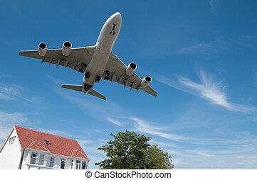 large jet aircraft landing approach over suburban housing