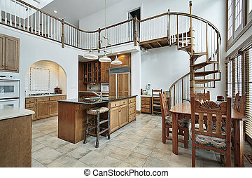 Large kitchen in luxury home with spiral stairway to second floor