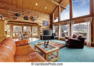 Large beautiful living room in log cabin house with leather chair and couch. View of rustic dining area from living room