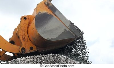 Large loader pours rubble from bucket, close-up, empty...