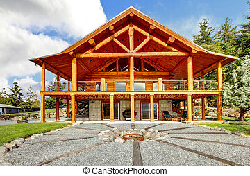 Large log cabin with porch and fire circle.