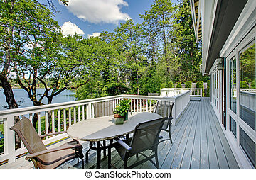 Large long balcony home exterior with table and chairs, lake...