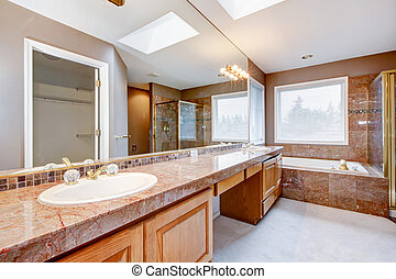 Large luxury bathroom with red granite countertops and tub....